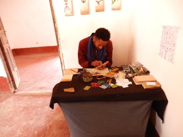 Artist painting onto wooden plaques to purchase